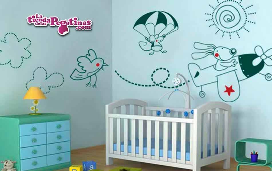 Diseño aplicado en una pared con el vinilo de un Perro en una avion, un raton paracaidista, nubes, un sol y un pajaro